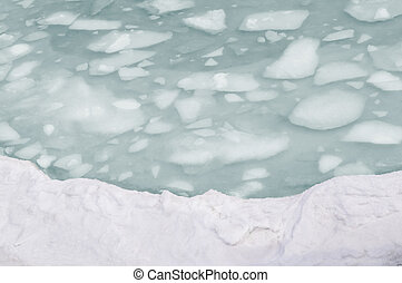 Ice floes float in the sea water in spring in the bay