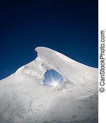 Ice formation illuminated by sun light and dark blue sky -...