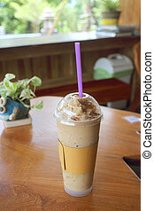 ice fresh coffee in plastic glass on wooden table