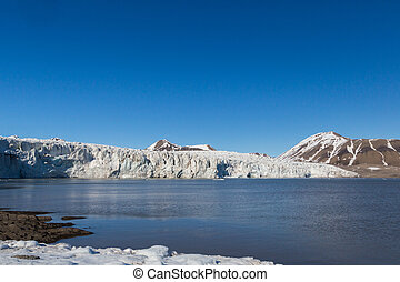 ice front of Esmarkbreen glacier in summer, Spitsbergen, blue sky, sea