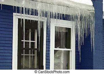 Winter freezing ice hanging on blue house