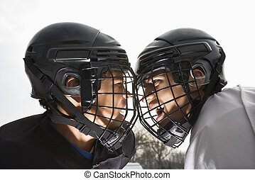 Ice hockey face off. - Two ice hockey players in uniform...