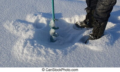 ice hole waterhole drill - fisherman with warm shoes...