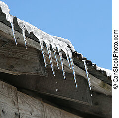 ice icicles on the roof that melt in the sun in winter