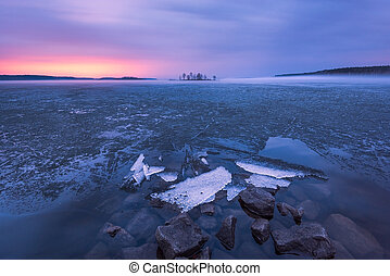 Ice melting on the lake in the sunset
