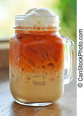 Ice milk tea - Thai cold milk tea was put in a glass with a ...