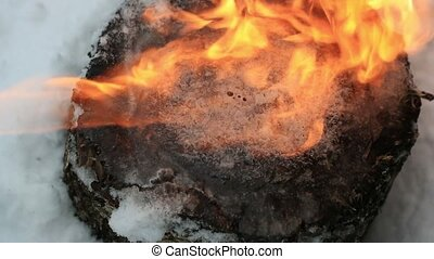 ice on a wooden stump melts under a stream of fire in slow motion