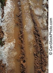 ice on mud red clay soil road with tyres lines