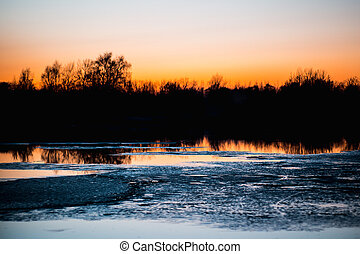 Ice on the river in forest at sunset