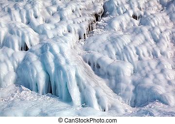 Ice over rocks wall on Baikal lake at winter time