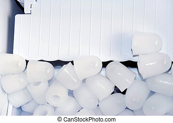 Ice pieces in ice maker - pieces of ice over white plastic...