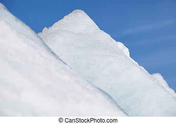 Ice pyramids on blue sky background.