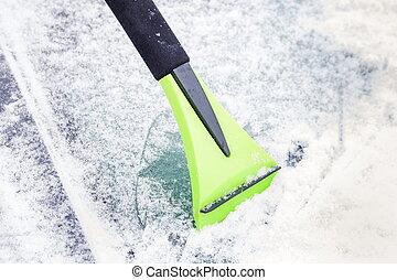 Ice scraper on car window