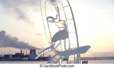 Ice sculpture of ballerina or female gymnast with gymnastic ribbon. Ice Sculptures in Russia. Sculptures In The Ice town at evening sunset.