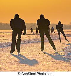 Ice Skaters on frozen lake at orange sunset