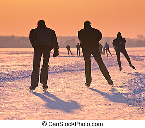 Ice Skaters on frozen lake at sunset