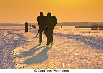 Ice Skaters on frozen lake under setting sun