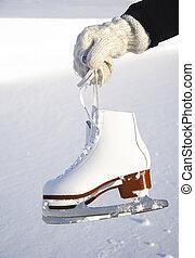 Ice skates. Closeup of female hand holding ice skates...