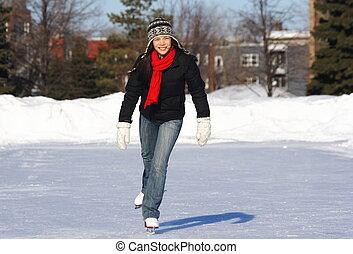 Ice skating - Beautiful young woman skating outdoors in...