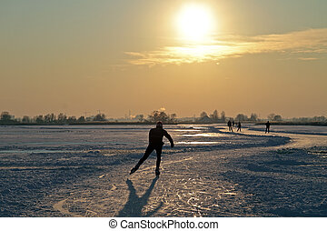 Ice skating in the countryside from the Netherlands at sunset