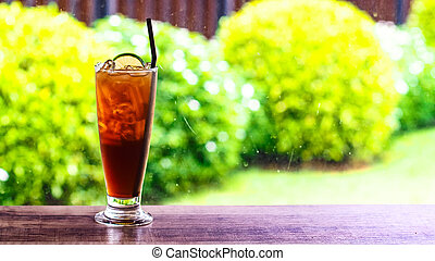 ice tea with slice of lemon in glass on the wooden rustic background with blur green nature trees of summer