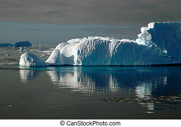 Iceberg in sunlight with water reflection
