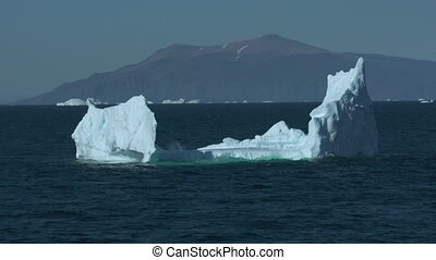 Handheld, medium wide shot of icebergs in a body of water with mountains in the background.