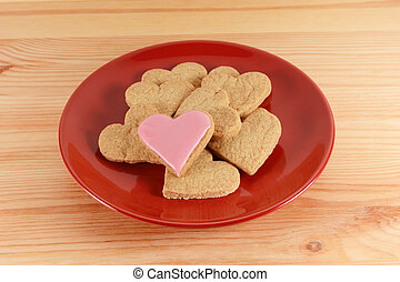 Iced and plain heart-shaped biscuits piled on a red plate