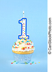 Iced birthday cupcake with with lit number 1 candle and sprinkles