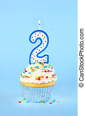 Iced birthday cupcake with with lit number 2 candle and sprinkles