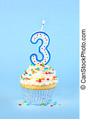 Iced birthday cupcake with with lit number 3 candle and sprinkles