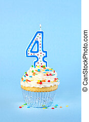 Iced birthday cupcake with with lit number 4 candle and sprinkles