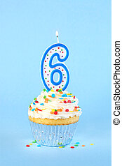Iced birthday cupcake with with lit number 6 candle and sprinkles