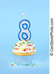Iced birthday cupcake with with lit number 8 candle and sprinkles