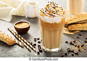 Iced caramel latte coffee in a tall glass with syrup and...