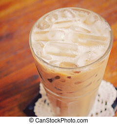 Iced coffee on wooden table with retro filter effect