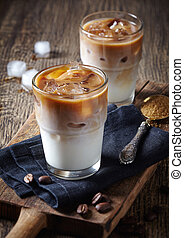 Two glasses of iced coffee on wooden background