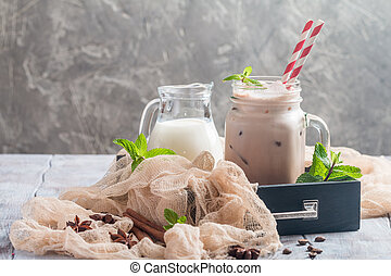 Iced coffee with milk in glass jur on wooden table decorated...