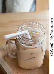 Iced coffee with milk is in Mason jar , on the table.