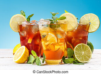 Iced tea - Glasses of iced tea with lemon, lime, orange and...