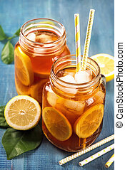 Iced tea with lemon in glass jars