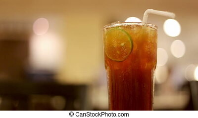 Iced tea with lime slice and blurred restaurant background