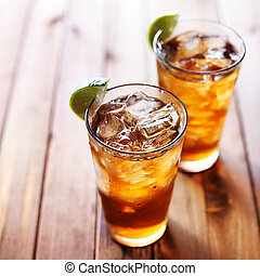 iced tea with lime wedges on wooden table and copy space ...