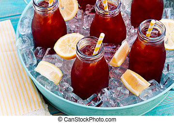 Iced Teas in Ice Filled Tray - Glass milk bottles filled...
