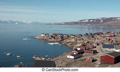 Houses in mountains on shore of of Greenland in Arctic Ocean...
