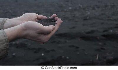 Iceland, black sand. Men's hands close up, handful of...