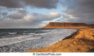 Amazingly lit Icelandic coastline. It's just before the sun sets and mountains in the background has a warm yellow evening color.