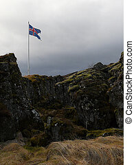 Icelandic flag above the rocks of Thingvellir, a fissure in the earth?s crust where the european and american continents slowly drift apart.