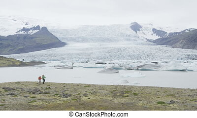 Iceland hiking travel people trekking by glacier. People by ...