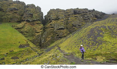 Iceland hiker tourist sightseeing visiting Raudfeldsgja Canyon gorge rift nature landscape on the Snaefellsnes peninsula, West Iceland. RED EPIC SLOW MOTION.